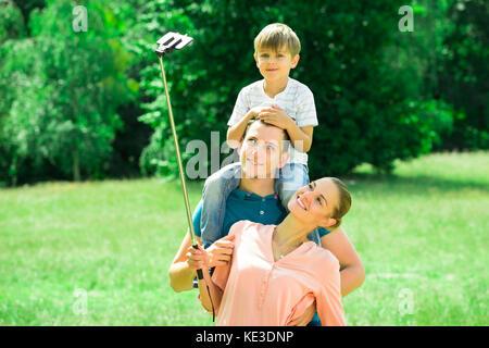 Sorridente giovane famiglia selfie tenendo in posizione di parcheggio Foto Stock