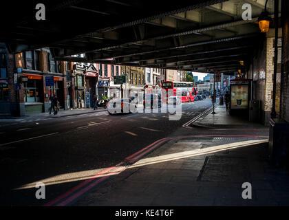 Uomo in bianco t shirt portando la sedia da ufficio sotto il ponte ferroviario in ombre su una strada di Londra Foto Stock