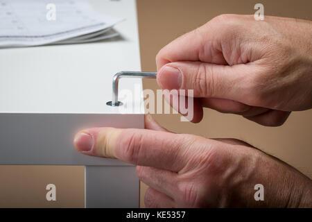 Un uomo che, costruendo flat pack mobili usando una chiave per viti a testa esagonale incassata con le istruzioni Foto Stock