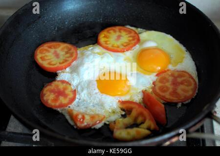 Due uova fritte in nero padella e fette di pomodoro. processo di cottura. Foto Stock