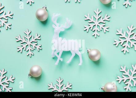 Elegante natale anno nuovo biglietto di auguri poster renne bianco fiocchi di neve sfere pattern sul turchese sfondo blu. copia spazio. stile scandinavo. Foto Stock