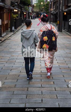 Una geiko e il suo accompagnatore a piedi giù per una strada in Gion, Kyoto Foto Stock