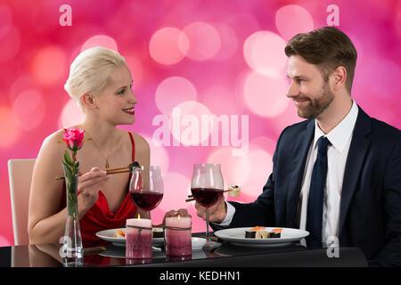 Ritratto di giovane coppia felice di mangiare sushi in un ristorante a sfondo bokeh di fondo Foto Stock