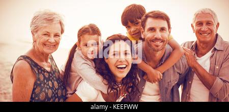 Ritratto di sorridere la famiglia felice in posa in spiaggia Foto Stock