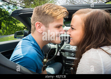 Felice coppia giovane seduto in un auto guardando ogni altro Foto Stock