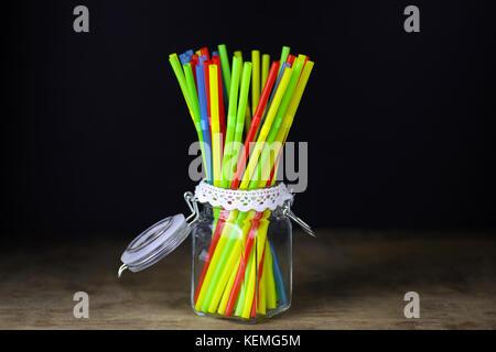 In plastica colorata tubi cocktail in piedi in un bicchiere Foto Stock
