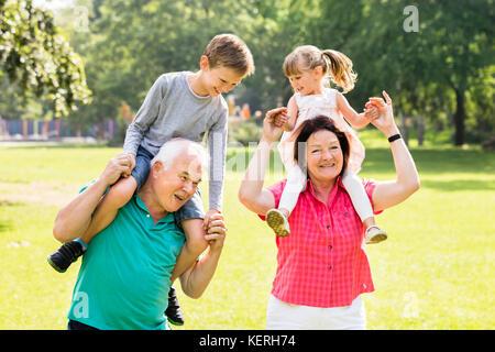 Felice nonni offrendo divertimento piggyback ride ai loro nipoti in posizione di parcheggio Foto Stock