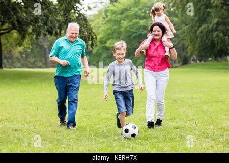 La famiglia felice che giocano a calcio gioco insieme in esecuzione per la sfera Foto Stock