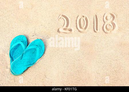 Blue coppia di flip flop sulla spiaggia, 2018 scritto nella sabbia Foto Stock