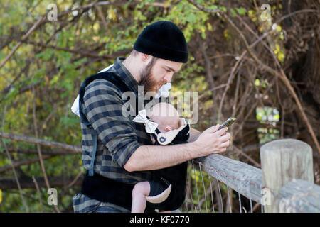 La millenaria papà con bambino in gestore al di fuori di parlare e scrivere messaggi Foto Stock