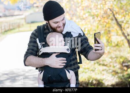 La millenaria papà con bambino in gestore al di fuori di Walking & tenendo Selfies con telefono Foto Stock