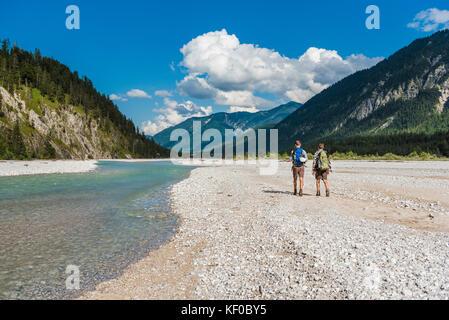 In Germania, in baviera, vista posteriore di due escursionisti con zaini a piedi nel letto asciutto del torrente Foto Stock