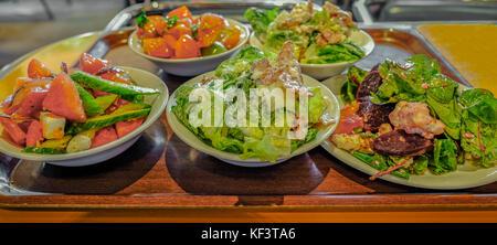 Piastre di diverse insalate su una tavola di legno cercando vassoio. Scelte di insalate presso la mensa. Foto Stock