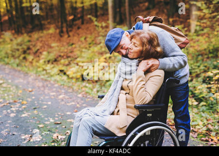 Coppia senior con la sedia a rotelle in autunno foresta. Foto Stock