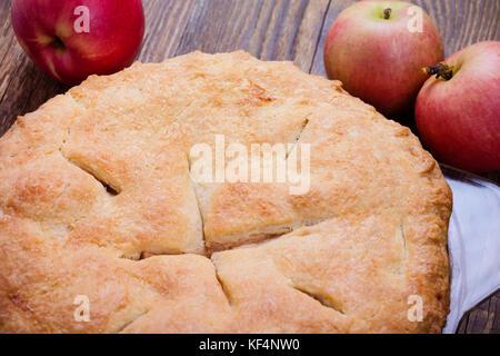 In casa tradizionale autunno torta di mele con un grafico a torta in scaglie crosta in tavola in legno rustico Foto Stock