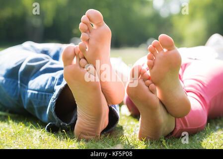 Close-up del paio di piedi sdraiati sull'erba a park Foto Stock