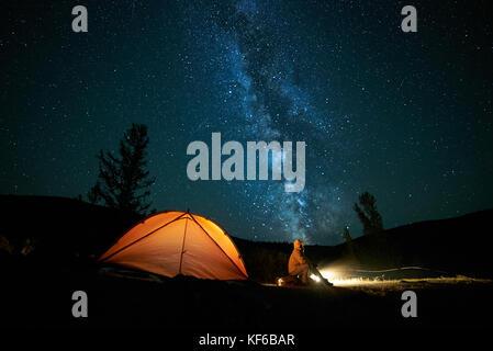 Tourist vicino al suo accampamento tenda a notte. Foto Stock