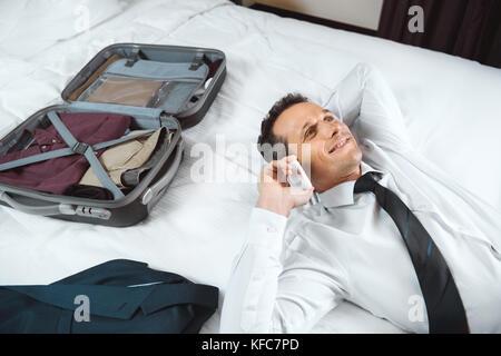 Imprenditore parlando al telefono sul letto Foto Stock
