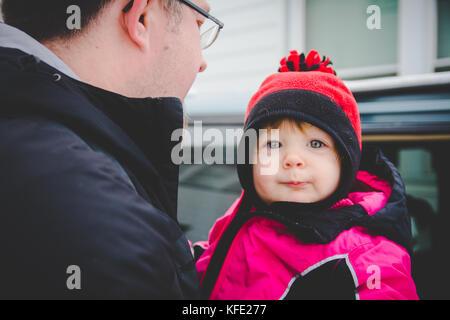 Uomo che porta bambino per auto in abbigliamento invernale Foto Stock