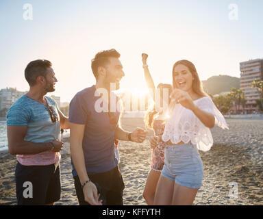 Ritratto di giovane donna graziosa ballare con gli amici sulla spiaggia Foto Stock