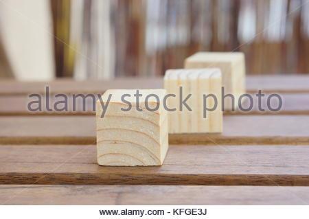 Tre giocattolo di legno blocchi giacenti su un tavolo in soft focus Foto Stock