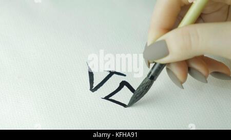 Donna con le mani in mano la scrittura cinese. hieroglyph mano femmina tenendo un pennello di scrittura calligrafia Foto Stock