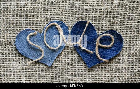 Elegante iscrizione da vendita di spago nella mia mano su due denim senecah sullo sfondo di tela in tessuto per Foto Stock