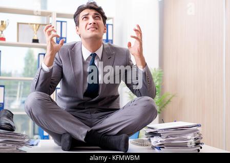 Imprenditore seduto sulla parte superiore della scrivania in ufficio Foto Stock