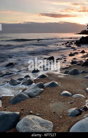 Un bellissimo e suggestivo paesaggio marino con rocce umide in primo piano e la spiaggia di sabbia con le onde che Foto Stock