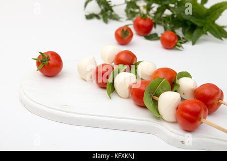 Caprese di mozzarella, pomodoro cherry e basilico, tradizione mediterranea, snack su bianco Foto Stock