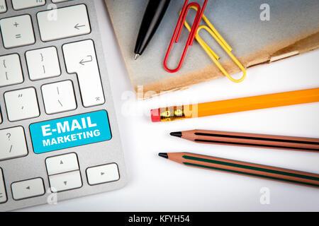 E-mail marketing concetto. tastiera del computer su un bianco scrivania da ufficio con vari oggetti Foto Stock