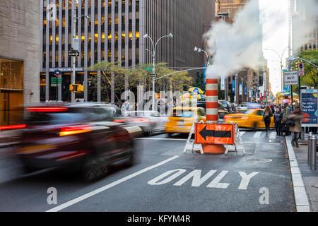 Ogni giorno a New York. Il traffico in 49 th Street e il tubo del vapore Foto Stock