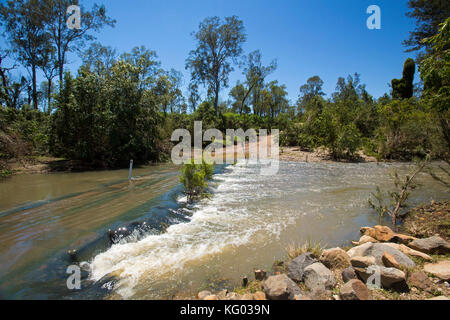 Acque alluvionali del fiume kolan nella regione di bundaberg ruggente su strada rurale che rende impraticabile dopo Foto Stock