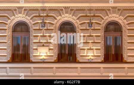 Tre finestre in fila nella notte illuminata facciata di urban ufficio edificio vista frontale, San Pietroburgo, Foto Stock