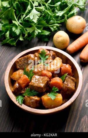 Gulasch, spezzatino di carne con verdure nella ciotola sul tavolo di legno Foto Stock