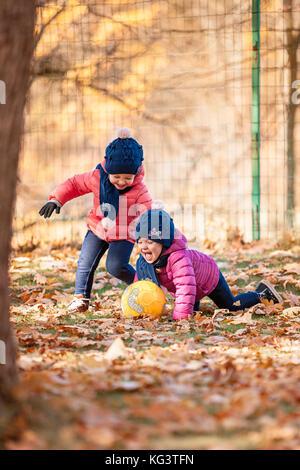 Le due piccole bambine bambino giocando in foglie di autunno Foto Stock