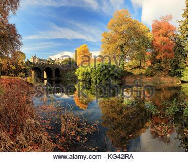 Autumn Tree e riflessioni a ponte da un laghetto in Drummond Castle Gardens. Crieff, Perth and Kinross. Foto Stock