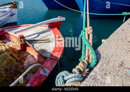 Attraccata colorate barche da pesca legato con la fune a un moor presso la porta locale. Foto Stock