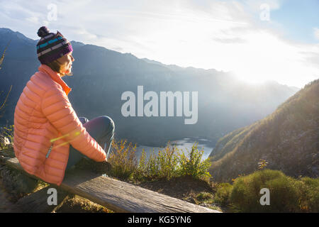 Giovane donna seduta sul ramo sul punto di vista, per rilassarsi dopo le escursioni e guardando il lago di Bohinj, Foto Stock