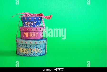 Pila di 3 regalo di Natale scatole legate con nastro isolato su sfondo verde Foto Stock