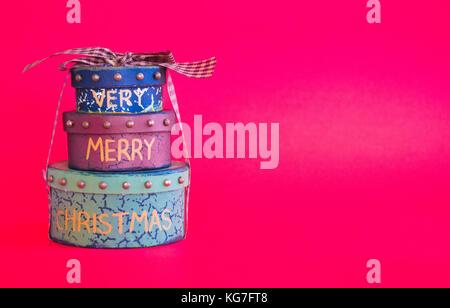 Pila di 3 regalo di Natale scatole legate con nastro isolato su sfondo rosso Foto Stock