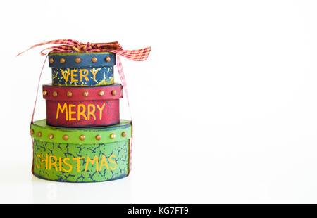 Pila di 3 regalo di Natale scatole legate con nastro isolato su bianco Foto Stock