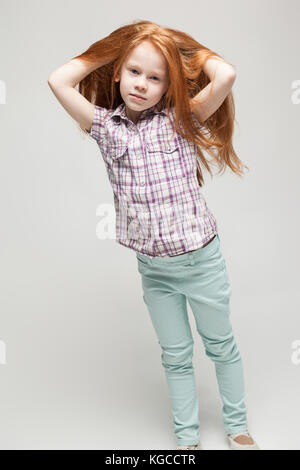 Pretty redhead bambina in plaid shirt, luminoso pantaloni blu e stivali bianco Foto Stock