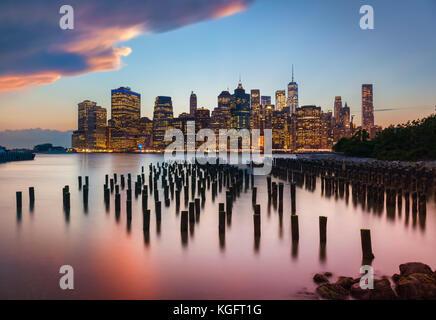 Skyline di Manhattan New York skyline tramonto tempestoso cielo sopra i grattacieli con Brooklyn molo vecchio 1 palificazioni di legno New York City Stato di New York STATI UNITI D'AMERICA Foto Stock