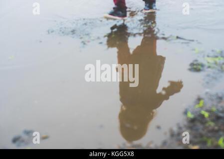 Bambino a camminare in una pozza di fango Foto Stock