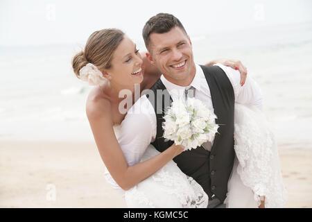 Lo sposo dando piggyback ride alla sposa sulla spiaggia Foto Stock