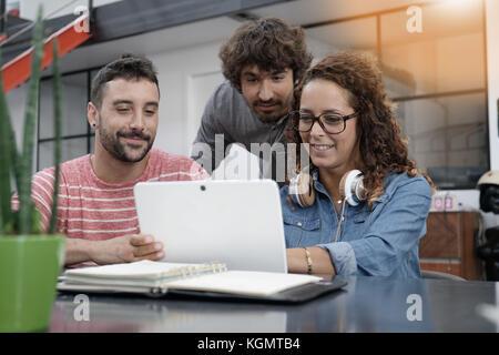 Giovani imprenditori lavora su tavoletta digitale Foto Stock