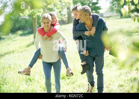 I genitori dando piggyback ride per bambini in campagna