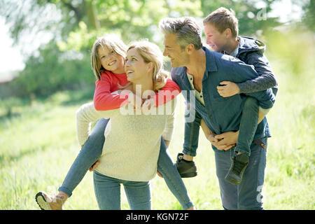 I genitori dando piggyback ride per bambini in campagna Foto Stock