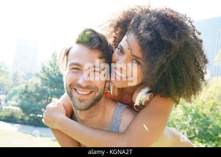 L uomo dando piggyback ride per donna a central park Foto Stock